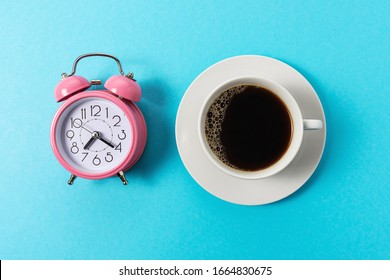 Creative layout made with cup of coffee and alarm clock on blue background. Minimal time concept.