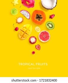 Kreatives Layout aus Drachenfrucht, Papaya, Kokosnuss, Kirsche, Kiwi, Erdbeere, Mango, Mangostanfrüchte, Carambola, Rambutan, Banane auf gelbem Hintergrund. Flat lay. Lebensmittelkonzept.