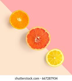 Creative layout made of grapefruit, orange, lemon. Flat lay. Food concept. Grapefruit, orange, lemon on pink and beige background.