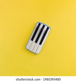 Creative layout made of gray mobile smart phone with piano keys, isolated on illuminating yellow background. Music communication fun idea. Minimal aesthetic, abstract, flat lay, surreal concept.
