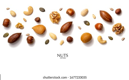Creative layout made of hazelnut nuts, almonds, walnut, peanut, pecan, sunflower seeds. Flat lay with copy space. Fresh food concept. Nuts isolated on white background.
