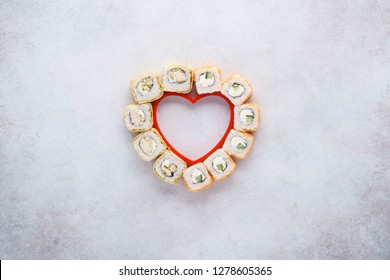 Creative layout made of heart shaped set of sushi rolls for Valentine's Day. Menu or delivery concept with space for text.