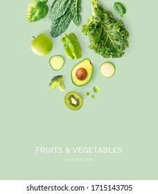 Kreatives Layout aus kale, broccoli, grüne Bohnen, Zucchini, Gurken, Apfel, Kiwi, Zitronengras auf grünem Hintergrund. Flat lay. Lebensmittelkonzept. Makrokonzept.