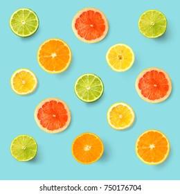 Creative layout made of lemon, lime, orange and grapefruit. Flat lay. Food concept. Lemon, lime, orange and grapefruit on turquoise background.