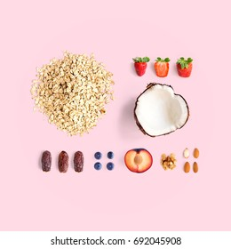 Creative layout made of oatmeal, coconut, strawberry, plum, dried dates, blueberry, almond and walnut. Flat lay. Food concept.