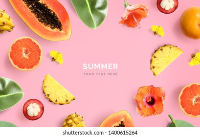 Creative layout made of papaya, grapefruit, pineapple, orange, mangosteen and flowers on pink background.  Tropical flat lay. Summer fruits concept.