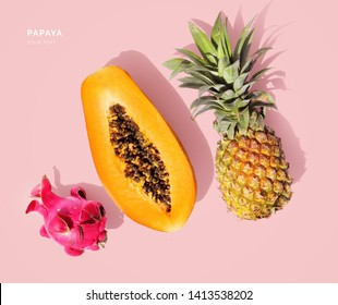 Creative layout made of papaya, pineapple and dragonfruit. Flat lay. Food concept. Papaya, pineapple and dragonfruit on pink background.