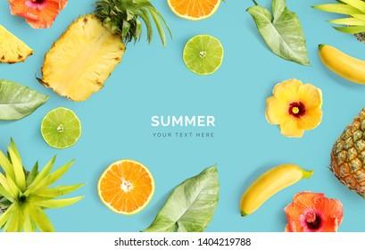 Kreatives Layout aus Ananas, Banane, orangefarbenen Früchten, Kalk und Blumen auf blauem Hintergrund.  Tropische flache Lage. Sommerfrüchte-Konzept.