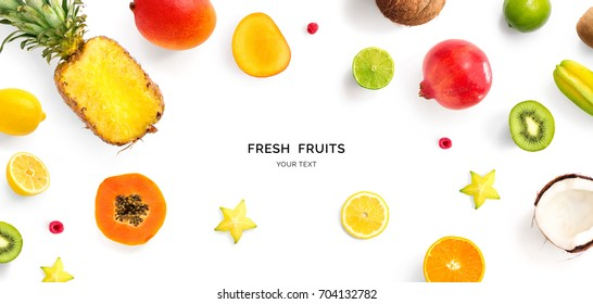 Creative layout made of pineapple, kiwi, lemon, lime, orange, papaya, coconut, pomegranate and carambola. Flat lay. Food concept.