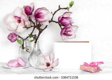 Creative layout made with pink magnolia flowers, empty card, macarons and gift box on white wooden background. mock up. still life. wedding frame. spring minimal concept