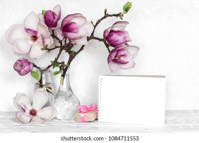 Creative layout made with pink magnolia flowers, empty card and gift box on white wooden background. mock up. still life. wedding frame. spring minimal concept