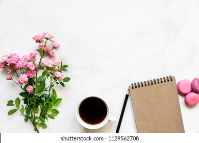creative layout made of pink rose flowers bouquet, coffee cup, blank notebook and macaroons over white marble table with copy space. top view. mock up. holiday concept