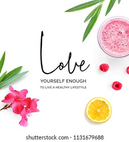 "Creative layout made of  quote ""Love yourself enough to live a healthy lifestyle"".  Tropical flat lay. Food concept. Lemon, raspberry, pink flowers and juice on the white background."
