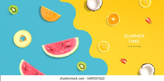 Creative layout made of summer fruits. Flat lay. Food concept. Macro concept. Watermelon, lemon, kiwi, melon, coconut, orange and strawberry on blue and yellow background.