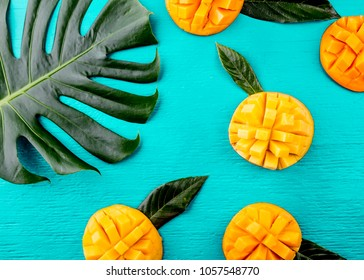Creative layout made of summer tropical fruits mango and tropical leaves on turquoise background. Flat lay. Food concept. Tropical concept.