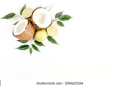 Creative layout made of summer tropical fruits: coconut, lime and leaves ficus. Food concept. flat lay, top view