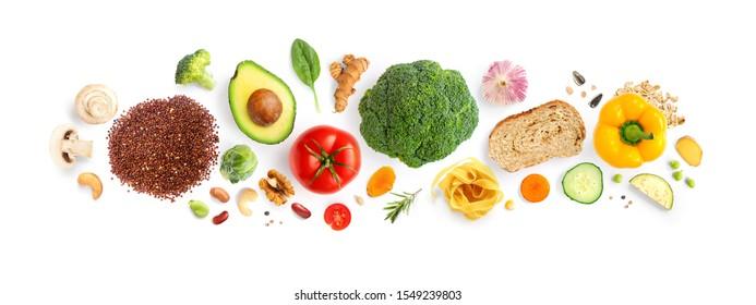 Kreatives Layout aus Walnüssen, Cashew, Avocado, Tomate, Broccoli, Brot, Nudeln, Pfeffer, Curcuma, Reis und Knoblauch auf weißem Hintergrund. Flat lay. Lebensmittelkonzept. Makrokonzept.