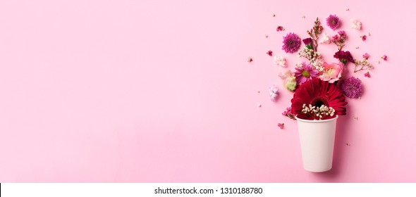 Creative layout made of white paper cup with pink flowers. Flat lay, top view. Banner with copy space. Valentines day, Woman day concept. Spring or summer banner with copy space.