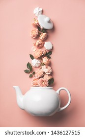 Creative layout made of whte tea pot with orange roses and merengues  on pink background, flat lay