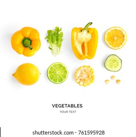 Creative layout made of yellow pepper, lemon, lime, corn and lettuce. Flat lay. Food concept. Yellow vegetables isolated on white background.