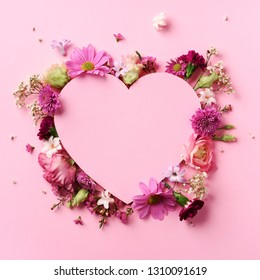 Creative layout with pink flowers, paper heart over punchy pastel background. Top view, flat lay. Spring, summer or garden concept. Present for Woman day. Square crop.