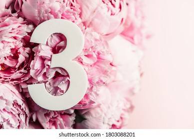 Creative layout. Pink peony flowers and digit three 3. Birthday greeting card. Anniversary concept. Top view. Copy space. Stylish white numeral over flowers background. Numerical digit