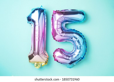 Creative layout. Rainbow foil balloon number, digit fifteen. Birthday greeting card with inscription 15. Anniversary concept. Top view. Stylish colored numeral on blue background. Numerical digit.