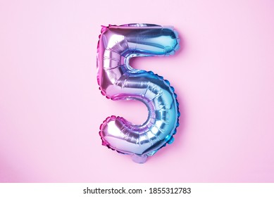 Creative layout. Rainbow foil balloon number and digit five 5. Birthday greeting card. Anniversary concept. Top view. Copy space. Stylish colored numeral over pink background. Numerical digit