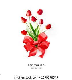 Creative layout with red tulip spring flowers and ribbon bow isolated on white background. Floral composition with beautiful fresh tulips. Valentine day concept, flat lay, copy space