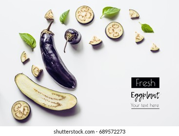 Creative layout from a solid and sliced eggplant on a white background with space for text. Vegetables isolated on white background. View from above