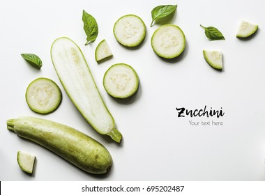 Creative layout of solid and sliced zucchini on white background with space for text. Isolated vegetables on white background. View from above