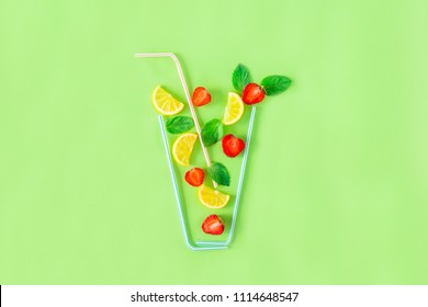 Creative layout strawberry lemonade ingredients - lemon, mint, berries falling in glass made with cocktail straws on green background. Summer drinks. Minimal food concept. Selective focus. Copy space