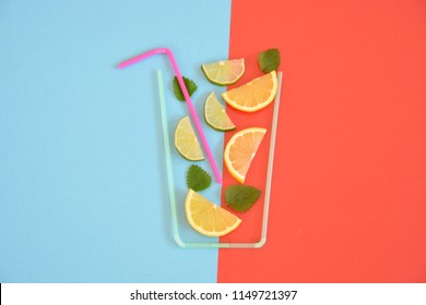 Creative layout strawberry lemonade ingredients - lemon, citrus, ice falling in glass made with cocktail straws on colorful background. Summer drinks. Minimal food concept. Selective focus.