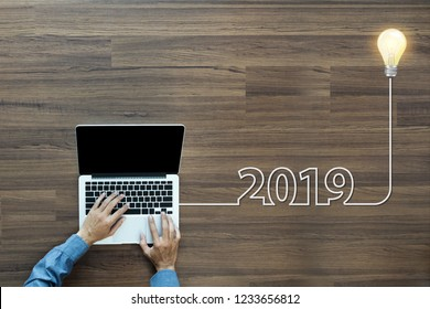 Creative light bulb idea 2019 new year, With businessman working on laptop computer PC, Top view from above