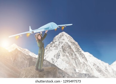 Creative little boy in aviator costume holding big blue crafted airplane above his head and pretending to fly high over the mountains, Child game and imagination concept, Space for text