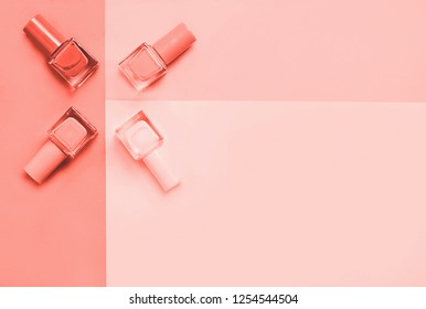 Creative Living Coral colored flat lay of fashion bright nail polishes on a living coral background. Minimal style. Color of the year 2019 concept. blogger concept. 16-1546