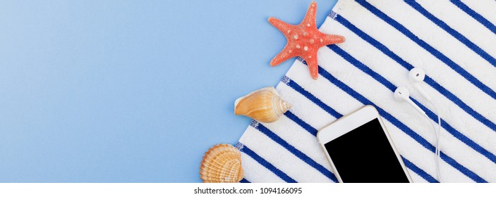 Creative long wide banner flat lay concept of summer travel vacations. Top view of beach towel, seashells, starfish and smartphone on pastel blue background with copy space in minimal style, template