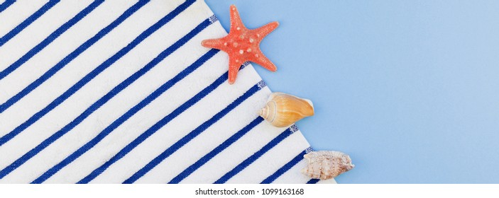 Creative long wide banner flat lay concept of summer travel vacations. Top view of beach towel and seashells and starfish on pastel blue background with copy space in minimal style, template