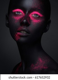 Creative make-up and beauty body art theme: portrait of a beautiful young girl model with black skin and pink shadows on her face, a beautiful pigment on a dark background in the studio.