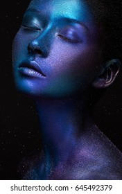 Creative make-up and beauty theme: beautiful girl model with cosmic make-up on face and body blue and purple skin color on dark background in studio