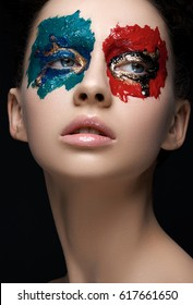Creative make-up and beauty theme: portrait of a beautiful young girl model with multi-colored paint in front of a dark background in the studio