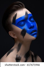 Creative make-up and body art theme: portrait of a beautiful young girl model with a blue make-up mask and black strokes of paint on her face on a dark background in the studio