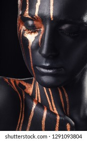 Creative makeup. Closeup portrait of woman an amazing woman with black makeup and leaking gold paint