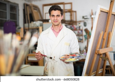 Creative male artist drawing picture with oil paints in studio
