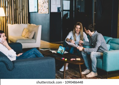Creative male and female designers analyzing plan for cooperation satisfied with productive job in office,positive employees discussing ideas while their colleague talking on mobile phone during work
