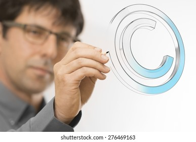 Creative man drawing copyright symbol on a transparent wall. Engineering background concept over white.