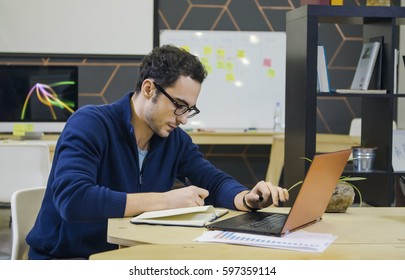 Creative man making notes at his workplace