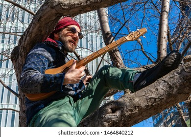Creative man sits in tree by skyscraper. A bearded man wearing red bandanna and green trousers is seen sitting in a city tree by a commercial high-rise, holding a small acoustic guitar.