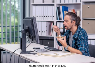 creative man is working in his office and eating granola