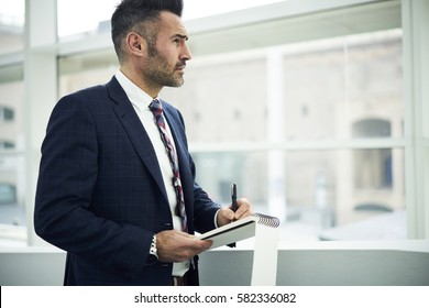 Creative manager of media marketing working on office of trading corporation inspiring of job process developing right advertising campaign to attract customers writing down best ideas into notebook